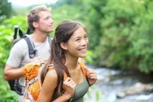 People hiking - happy hiker couple trekking as part of healthy l