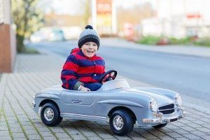 Happy Little Boy Driving Big Toy Car And Having Fun, Outdoors